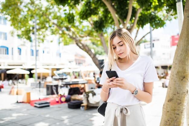 Jonge blonde vrouw lopen en typen op telefoon in de straat op een zonnige zomerdag