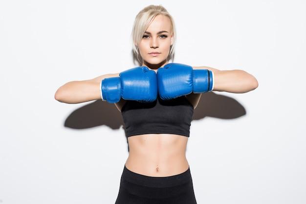 Jonge blonde vrouw met blauwe bokshandschoenen bereid om op wit te vechten