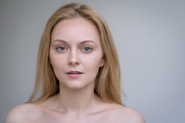 Jonge blonde vrouw met blote schouders die de huidverzorgingsindustrie vertegenwoordigen