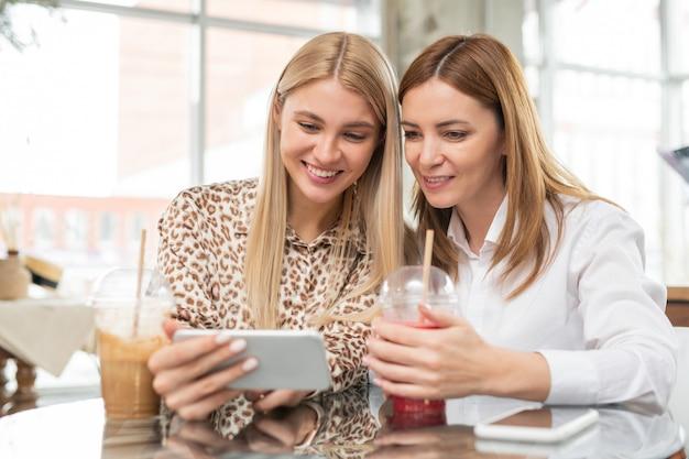 Jonge blonde vrouw met brede glimlach toont nieuwe foto's in smartphone aan haar moeder terwijl beiden genieten van rust in café na het winkelen