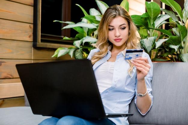 Jonge blonde vrouw met creditcard en met behulp van laptopcomputer.
