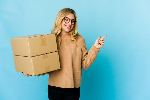 Jonge blonde vrouw met dozen om glimlachend en opzij te wijzen, iets op lege ruimte te laten zien