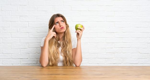 Jonge blonde vrouw met een appel die twijfels heeft