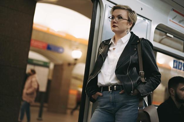 Jonge blonde vrouw met een bril die met de metro naar haar werk gaat en er moe uitziet?