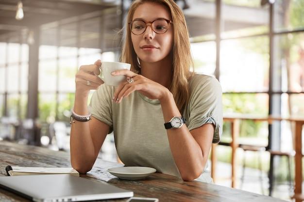 Jonge blonde vrouw met een bril in café