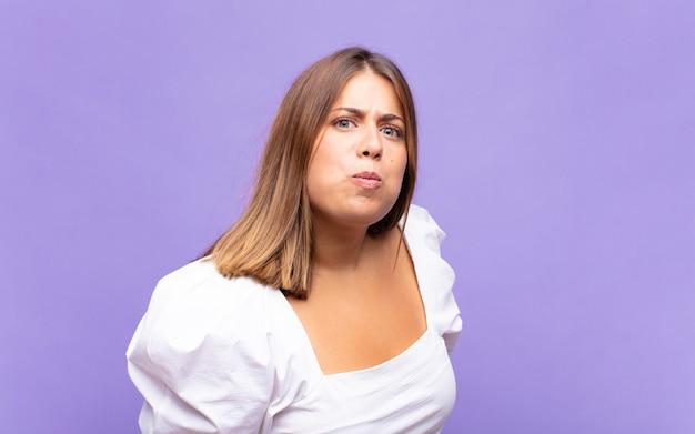 Jonge blonde vrouw met een gekke, gekke, verbaasde uitdrukking, puffende wangen, zich gevuld, dik en vol eten