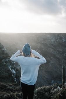 Jonge blonde vrouw met een hoed lopen op een rotsachtige zeekust in een winderig weer