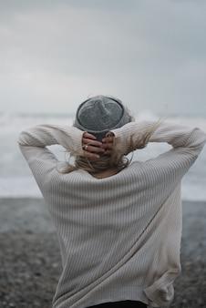 Jonge blonde vrouw met een hoed op het strand bij winderig weer