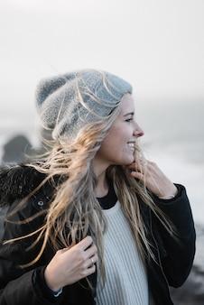 Jonge blonde vrouw met een hoed plezier op het strand bij winderig weer