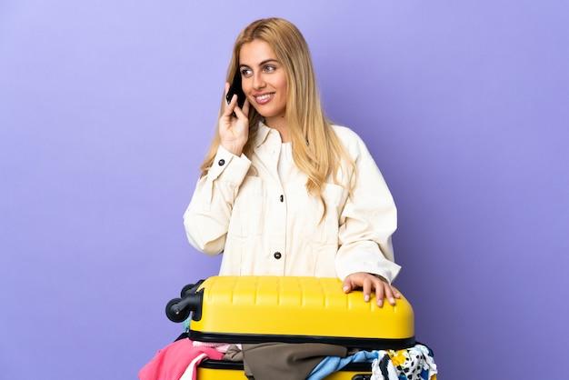 Jonge blonde vrouw met een koffer vol kleren over paarse muur houden een gesprek met de mobiele telefoon met iemand