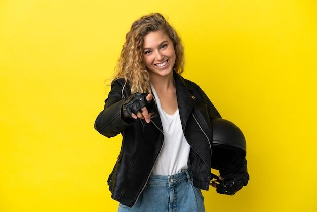 Jonge blonde vrouw met een motorhelm geïsoleerd op een gele achtergrond die naar voren wijst met een gelukkige uitdrukking