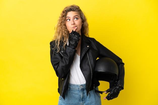 Jonge blonde vrouw met een motorhelm geïsoleerd op gele achtergrond met twijfels tijdens het opzoeken