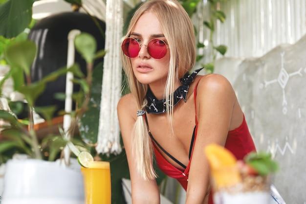 Jonge blonde vrouw met een rode stijlvolle zonnebril, vormt binnen