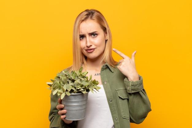 Jonge blonde vrouw met een slechte houding die er trots en agressief uitziet