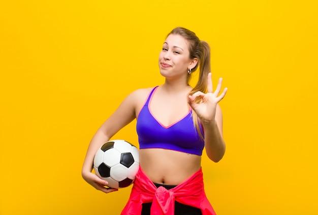 Jonge blonde vrouw met een voetbal. sport concept