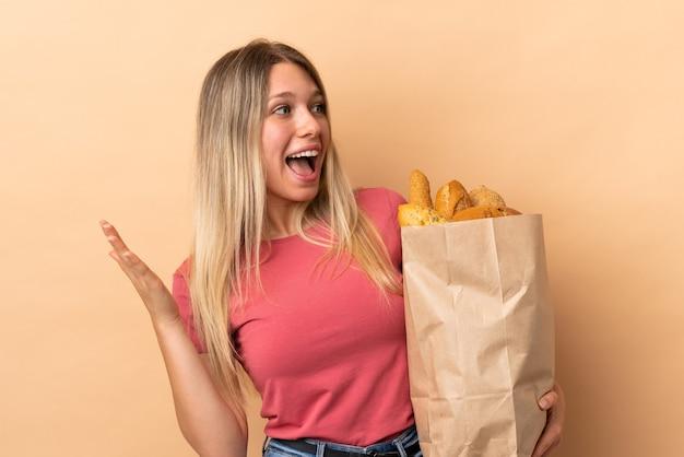 Jonge blonde vrouw met een zak vol brood geïsoleerd op beige muur met verrassingsgelaatsuitdrukking