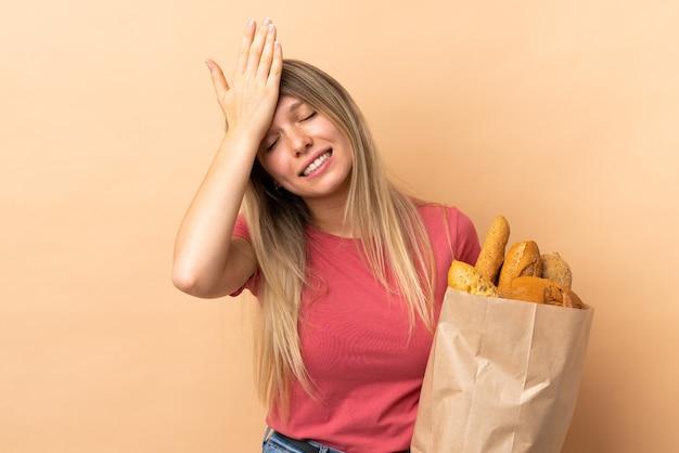 Jonge blonde vrouw met een zak vol brood geïsoleerd op beige muur twijfels met verwarren gezichtsuitdrukking