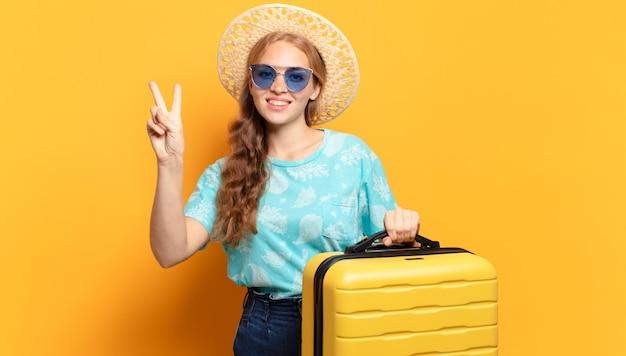 Jonge blonde vrouw met gele koffer. vakantie of reisconcept
