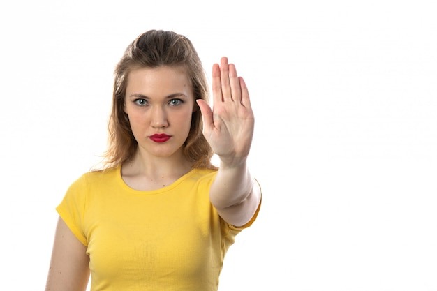 Jonge blonde vrouw met gele t-shirt stoppen