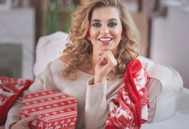 Jonge blonde vrouw met kerstcadeau