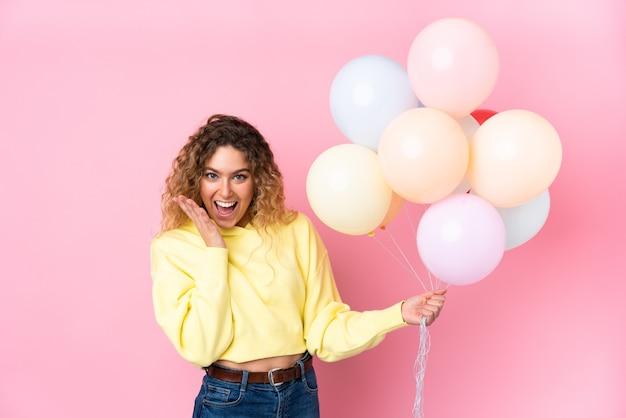 Jonge blonde vrouw met krullend haar die veel ballonnen vangen die op roze worden geïsoleerd met een verrassende gezichtsuitdrukking