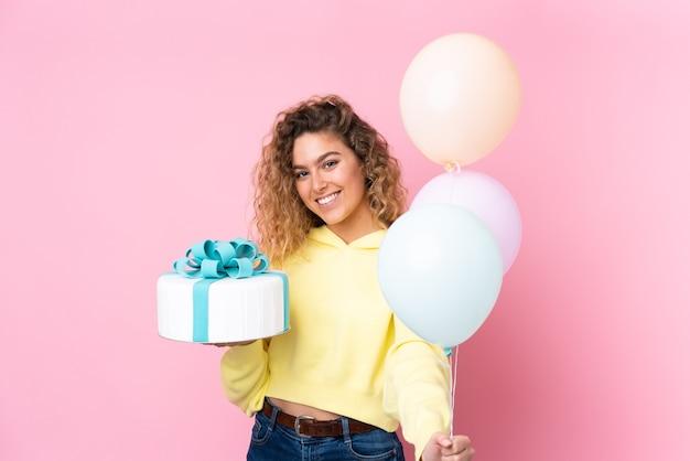 Jonge blonde vrouw met krullend haar die veel ballonnen vangt en een grote cake houdt die op roze muur wordt geïsoleerd