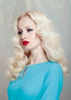 Jonge blonde vrouw met krullend haar en make-up, rode lippen, gekleed in een elegante blauwe jurk.
