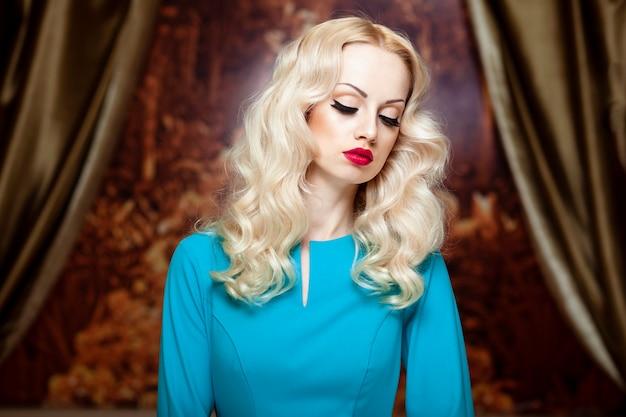 Jonge blonde vrouw met krullend haar en make-up, rode lippen, met gesloten ogen op een achtergrond van rapsodie