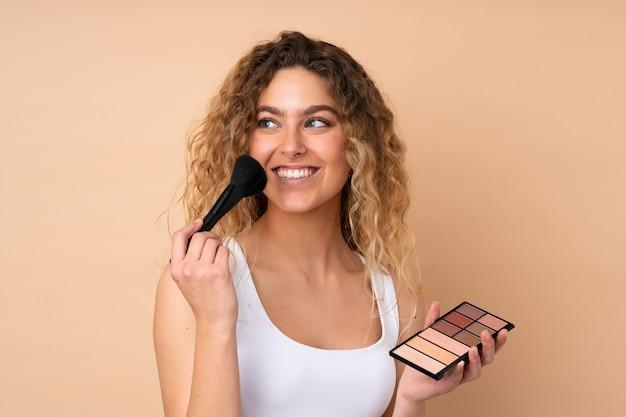 Jonge blonde vrouw met krullend haar geïsoleerd op beige muur met make-up palet en gelukkig