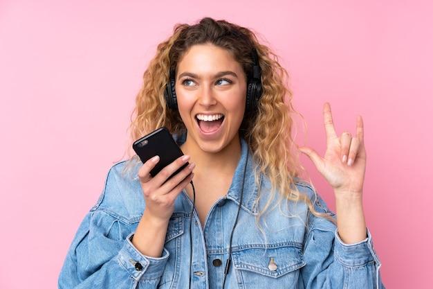Jonge blonde vrouw met krullend haar geïsoleerd op roze muur luisteren muziek met een mobiele rock gebaar maken