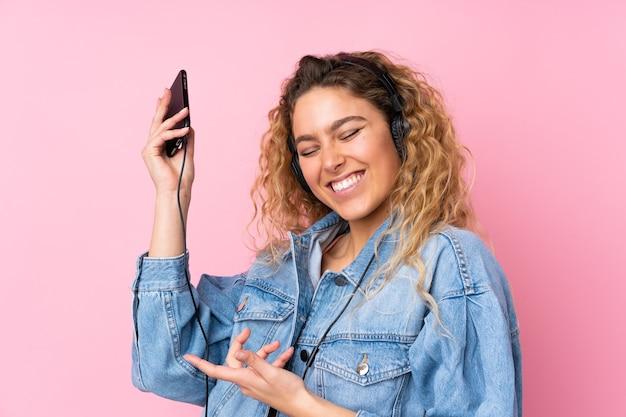 Jonge blonde vrouw met krullend haar geïsoleerd op roze muziek luisteren en gitaar gebaar doen
