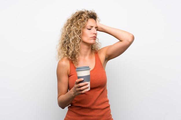 Jonge blonde vrouw met krullend haar met een take-away koffie met twijfels en met verwarren gezichtsuitdrukking