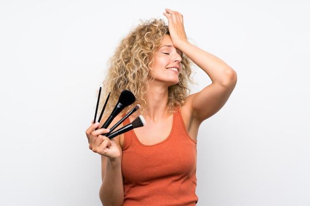 Jonge blonde vrouw met krullend haar met veel make-upborstel heeft iets gerealiseerd en de oplossing voor ogen