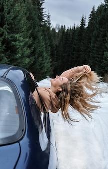 Jonge blonde vrouw met lang haar in de auto die de wind vangt