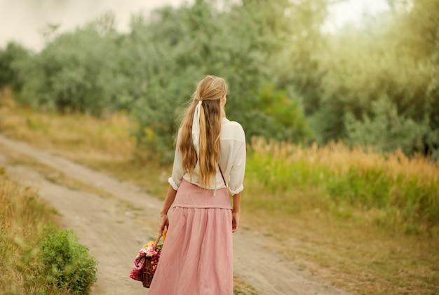 Jonge blonde vrouw met lang haar in retro stijl vintage kleding met picknickmand lopen op het land