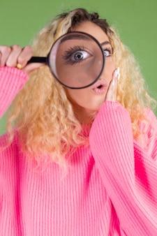 Jonge blonde vrouw met lang krullend haar in roze trui op groen met vergrootglas geschokt verrast
