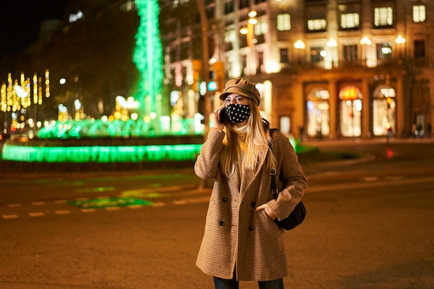 Jonge blonde vrouw met masker praten over de telefoon buiten 's nachts. op de achtergrond zijn er veel stadslichten. winterse sfeer.