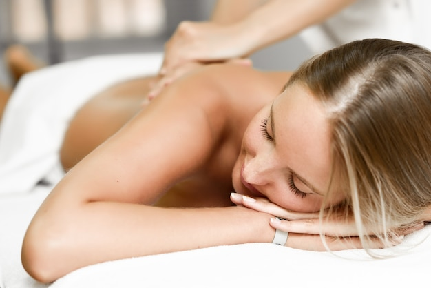 Jonge blonde vrouw met massage in de spa salon