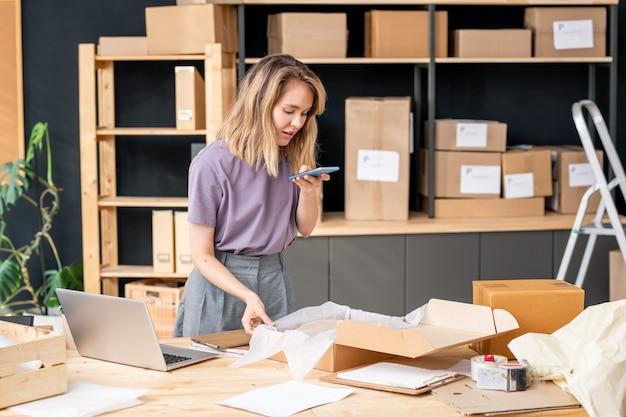 Jonge blonde vrouw met mobiele telefoon die een foto maakt van een opgevouwen trui in een doos voordat ze de bestelling inpakt en naar een van de klanten stuurt