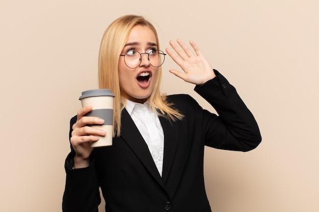Jonge blonde vrouw met open mond, geschokt en geschokt vanwege een vreselijke fout, handen opstekend