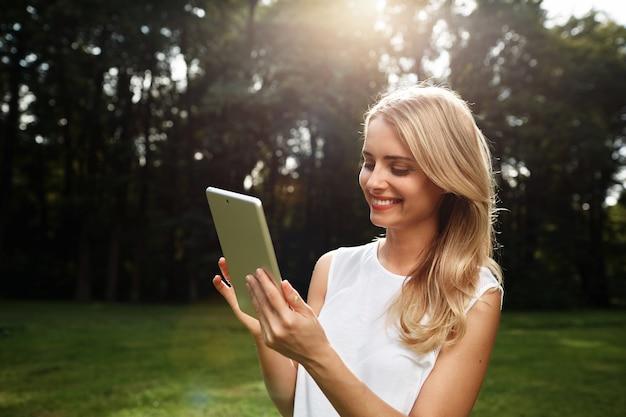 Jonge blonde vrouw met tablet
