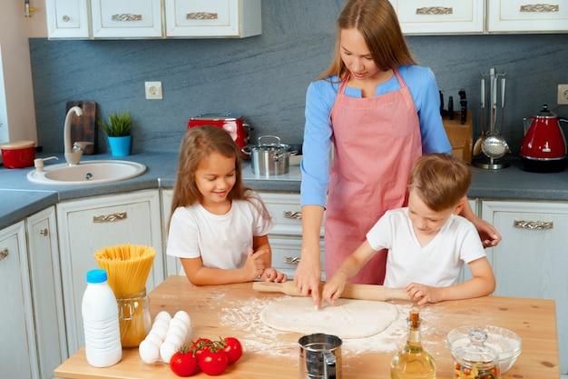 Jonge blonde vrouw, moeder en haar kinderen plezier tijdens het koken van deeg