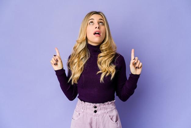 Jonge blonde vrouw naar boven met geopende mond