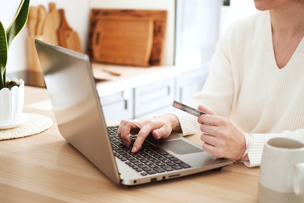 Jonge blonde vrouw online kopen met een creditcard op de laptop, thuis winkelen