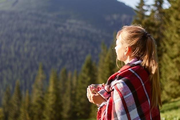 Jonge blonde vrouw ontspannen in de bergen