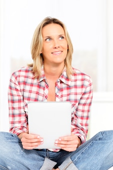 Jonge blonde vrouw op bank met tablet