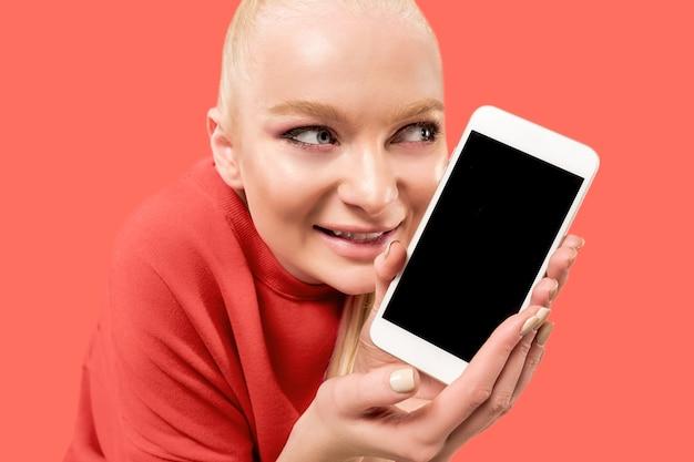 Jonge blonde vrouw op koraalachtergrond met smartphone