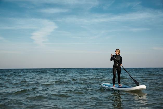 Jonge blonde vrouw op paddleboard op zee