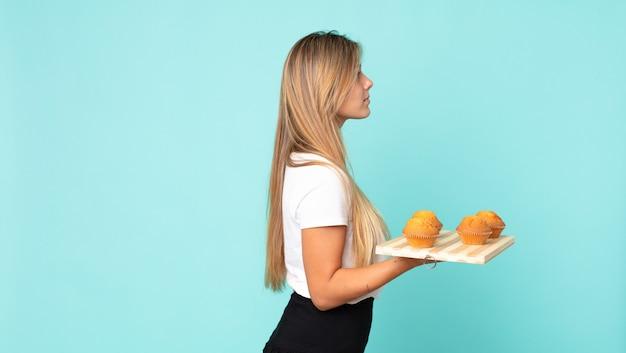 Jonge blonde vrouw op profielweergave denken, verbeelden of dagdromen en een muffins troy vasthouden