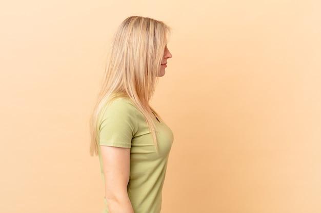 Jonge blonde vrouw op profielweergave denken, verbeelden of dagdromen